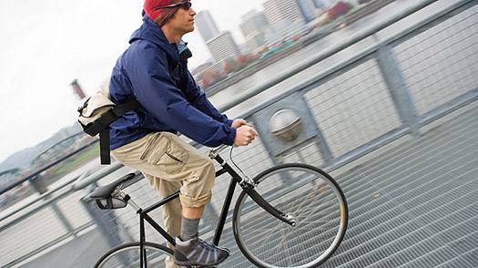B51JKR Male Cyclist Riding Across Bridge, near Portland, Oregon, USA