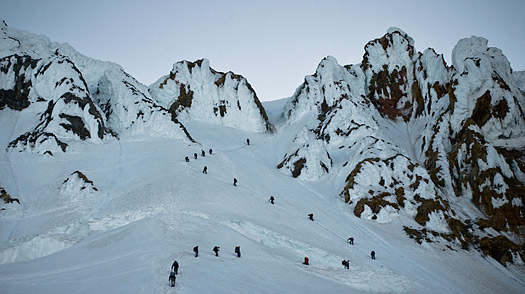 A large group of mountaineers ascend Mount Hood after the sun has set in Oregon.