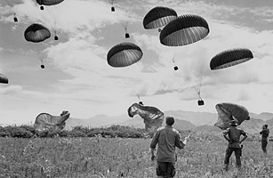 Special Forces Green beret troopers watch ammo cases dangling from parachutes come down into their drop zone near Dak Seang, Vietnam, June 20, 1968.