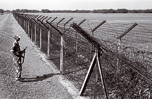 A soldier belonging to India's Border Security Force stands guard at the fence, scanning the Bangladeshi side for trouble