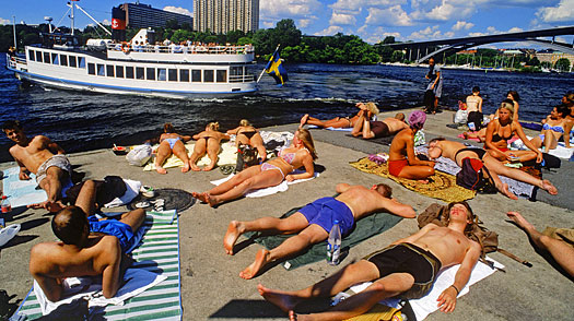 Sunbathers on cement pontoon at Langholmen Island in Stockholm with passing ferryboat on Riddarfjarden