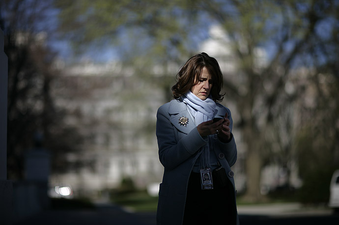A television producer checks her mobile before a White House event on the North Portico, March 29, 2007.