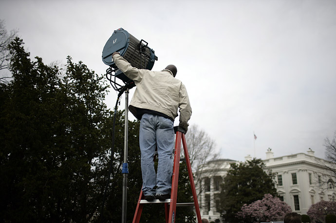 A technician adjusts a light during an event with President Bush on the South Lawn of the White House in Washington March 26, 2007.