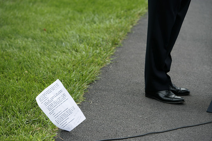 British Prime Minister Gordon Brown's notes blow to the ground during a joint press conference with President Bush at Camp David