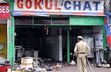 A policeman looks at a damaged restaurant, one of the sites of Saturday's bomb blast in Hyderabad, India, Sunday, August 26, 2007.