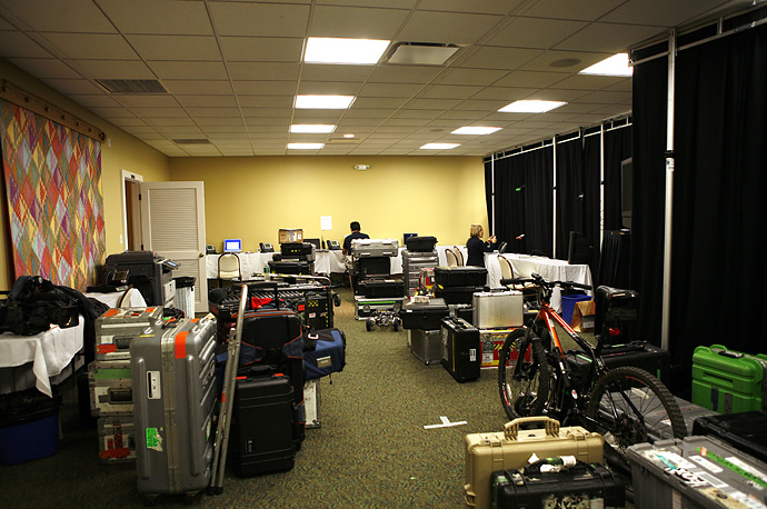 White House staffers work amid piles of gear and a bike in the temporary filing room for the traveling press in Kennebunkport, Maine.