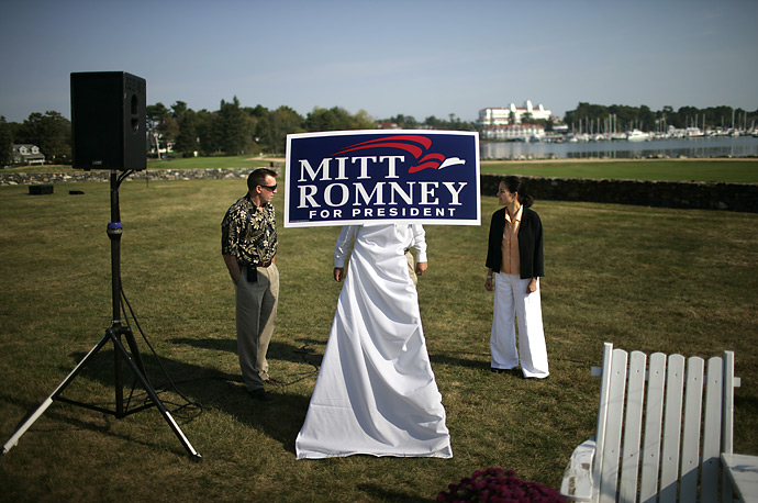 Campaign aides position a sign before an