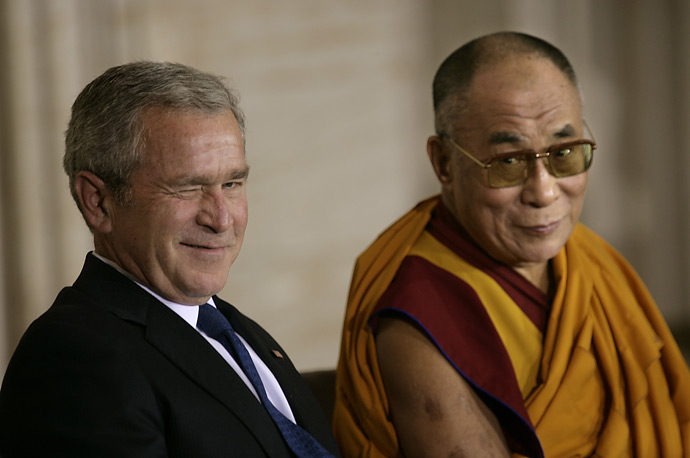 President George W. Bush winks at the crowd as he sits with the Dalai Lama at the start of ceremonies awarding the  exiled Tibetan leader the Congressional Gold Medal, October 17, 2007.