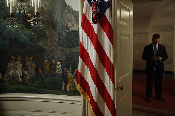A flag stands next to a mural in the White House's Indian Treaty Room, where President George W. Bush spoke about the situation in Burma, October 19, 2007.