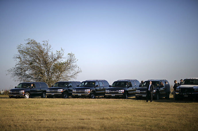 Secret Service wait with their vehicles as President George W Bush greets German Chancellor Angela Merkel at his Crawford, Texas ranch.