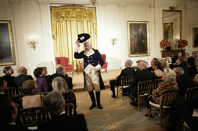 An actor playing General George Washington performs for  French President Nicolas Sarkozy and U.S. President George W. Bush in the East Room of the White House, November 6, 2007