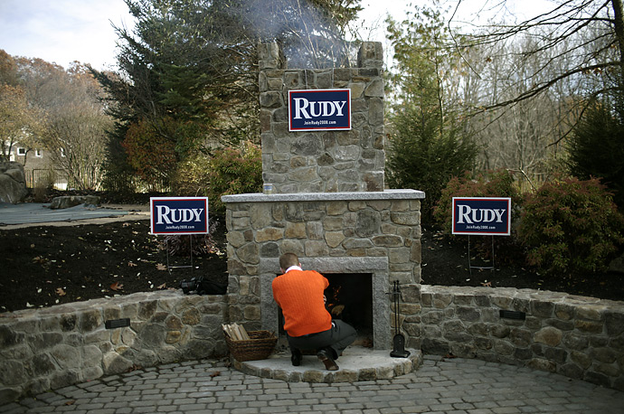 A supporter of Republican presidential candidate Rudy Giuliani tends an outdoor fire place during a campaign stop in Windham, N.H.,