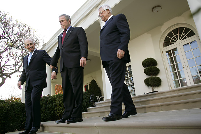 President George W. Bush positions Israeli Prime Minister Ehud Olmert, left, before making a statement with Palestinian President Mahmoud Abbas on the Annapolis Conference in the Rose Garden