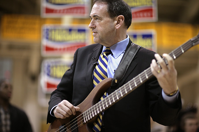 Republican presidential candidate Mike Huckabee jams on bass-guitar with the Tilton School rock band during a campaign stop in Tilton, New Hampshire.