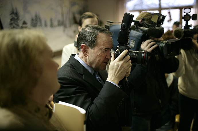 Republican presidential candidate Mike Huckabee, uses a press photographer's camera to take a picture of actor Chuck Norris, who he was campaigning with in Tilton, NH.