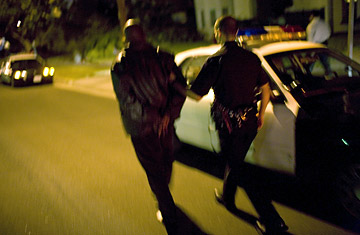 A Los Angeles Police Department leads a man suspected of kidnapping to a patrol car.