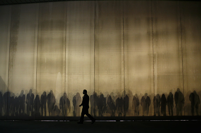 A man walks past the shadows of Mitt Romney supporters before an event in Long Beach, California.