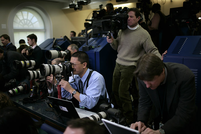 Media photographers work as President George W Bush holds a press conference at the White House in Washington.