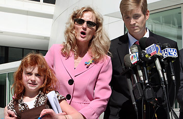Hannah Poling, left, stands with her parents Terry and Jon Poling, right, at a news conference in Atlanta on March 6, 2008.