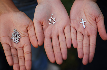 Three hands hold out the symbols of the three monotheistic religions.  Sèbastien Dèsarmaux / Godong / Corbis