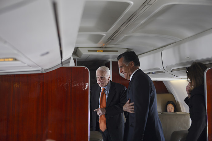 John McCain and Mitt Romney chat with passengers on a campaign flight to Denver, March 27, 2008.