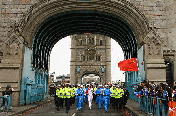 British athlete Paula Radcliffe (C) carries the torch past Chinese flags on Tower Bridge, central London.