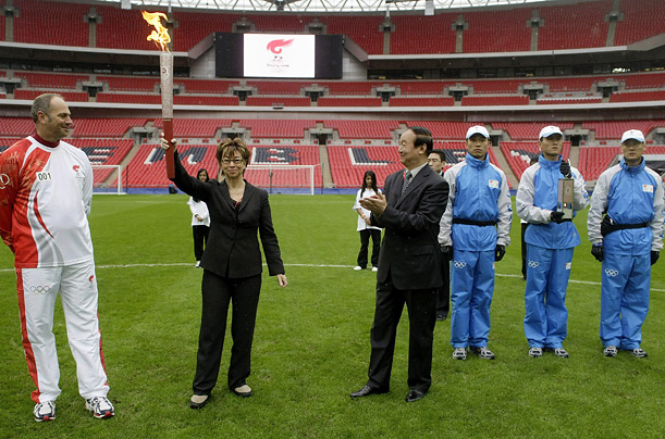 Sir Steve Redgrave, at left, watches Deputy Mayor of London, Nicky Gavron raise the torch aloft at the beginning of its relay through the London Streets. The Chinese Delegation look on.