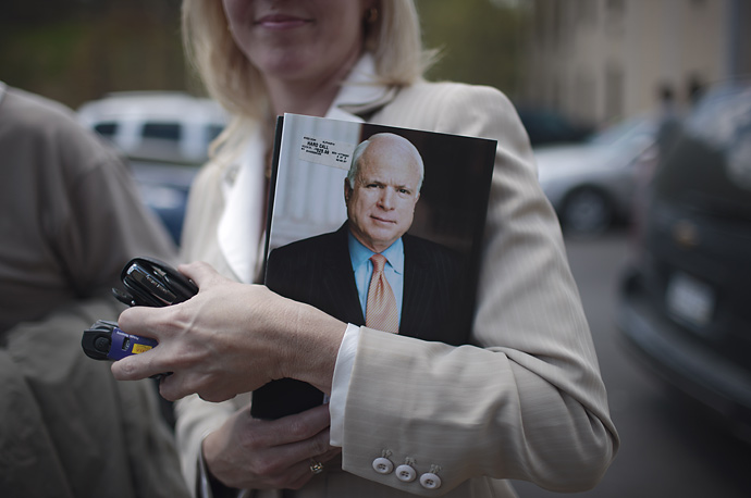 An autograph seeker holds John McCain's Hard Call: The Art of Great Decisions at the Old Martin County Courthouse in Inez, Kentucky