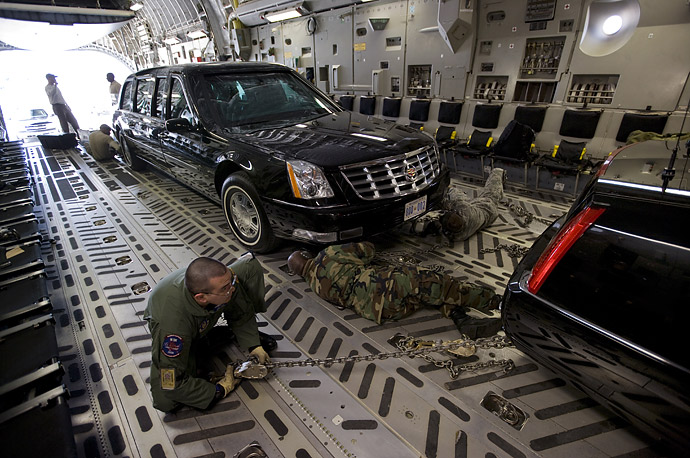 An Air Force crew secures two Presidential limousines inside a C5 military transport plane.  A