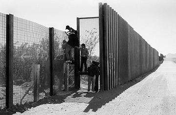 West of Naco, Arizona, some immigrants, including a 10-year-old boy, scale the new border fence in an effort to reach the States.