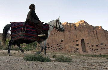 A horseman passes a mountain face where a giant Buddah once overlooked Bamiyan, Afghanistan.