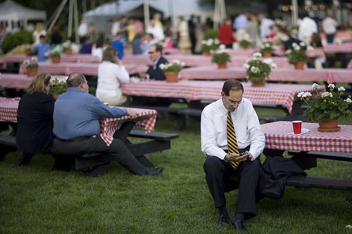 A guest checks his PDA at the Congressional Picnic on the South Lawn of the White House.