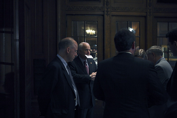 John McCain speaks with aides before a news conference after delivering a speech to the Economic Club of Canada in Ottawa.