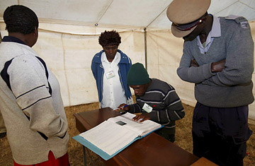 A policeman and voting officials check a voters identity on the register at a voting station in Harare, Zimbabwe, June 27, 2008.