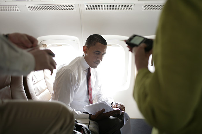 Barack Obama goes over notes with some aides aboard his campaign plane at the airport in Fargo, North Dakota.