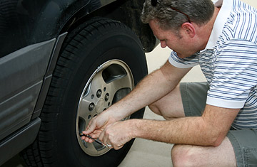 Man using tire gauge on tire of car