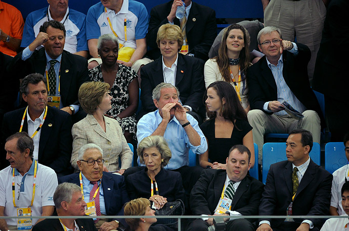 President George W Bush, his wife Laura, and daughter Barbara root for US swimmers at the finals at the Olympic National Aquatic Center, August 10, 2008.