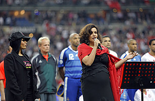 Tunisian singer Amina sings the Tunisian anthem before a soccer match between France and Tunisia. She is watched by Laam, a singer of Tunisian origin who, while singing the French national anthem was booed by fans at the stadium.