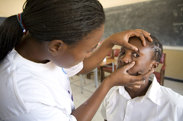 Beauty Chima, a teacher in Zambia, is pictured screening one of her pupils for eye problems