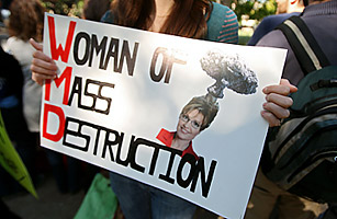 A woman holds an anti Sarah Palin sign.