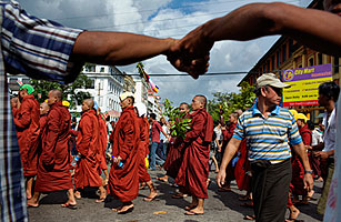 Monks protected by a 'human fence' of citizens holding hands walk in protest against the Burma's military regime on Sept. 25, 2007, in Rangoon