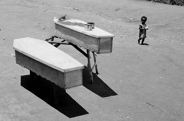 A child passes coffins in the village of Njuli, Malawi