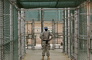 A Guantanamo guard watches over detainees, not pictured, in the exercise area at Camp 5 maximum-security facility at Guantanamo Bay U.S. Naval Base, Cuba. Seeking to e