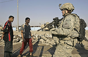A U.S. soldier secures the area at the scene where a roadside bomb exploded in Sadr City, Baghdad.