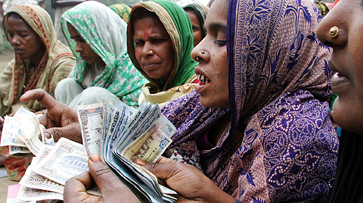 Bangladeshi women count money for repayment to a microcredit bank at Dowtia village, near Dhaka.