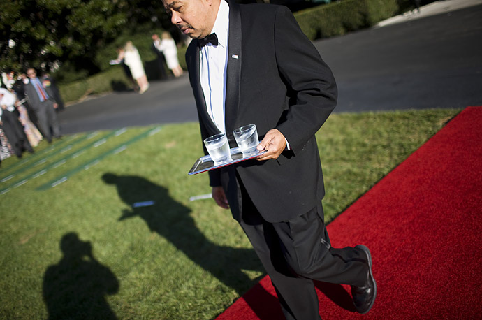A White House butler delivers 2 glasses of water to the podium before President George W Bush makes a speech on the South Lawn of the White House.