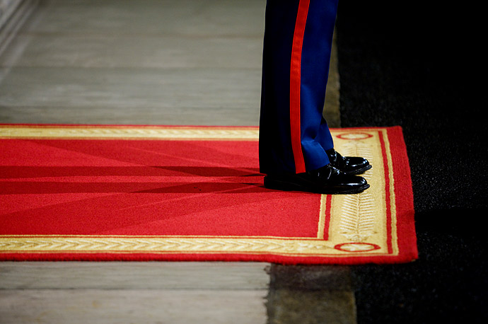 An honor guard Marine waits on a red carpet at the North Portico entrance of the White House.