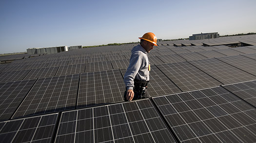 A solar technician employed by SunEdison checks the rooftop array of solar panels above the 514,000 square foot Walgreens distribution center in Woodland, Californi