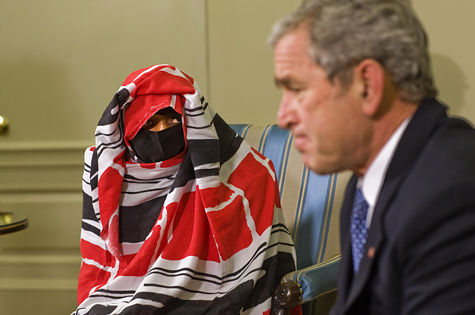 President Bush meets with Darfur human rights activist Dr. Halima Bashir in the Oval Office of the White House. Dr. Bashir covered her face from the cameras out of fear of reprisal.