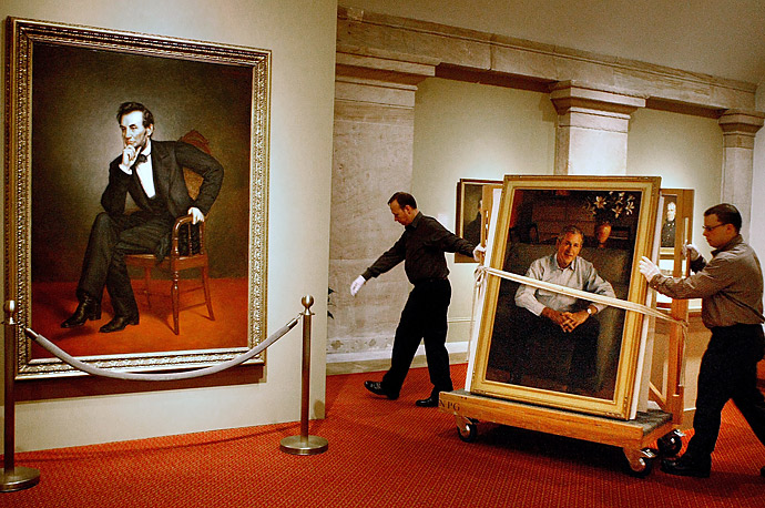 National Portrait Gallery Museum Technicians  wheel the official portait of President Bush past the portrait of Abraham Lincolin before hanging it at the gallery in Washington, DC.